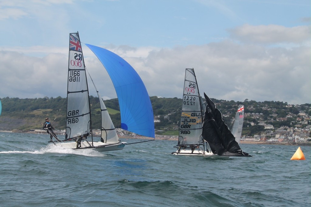 Lyme's Cameron and Darroll Moss, left, pursue the leaders Luke and Emma McEwan, at the leeward mark as spinnakers are dropped.  Photo by Jess Douglas