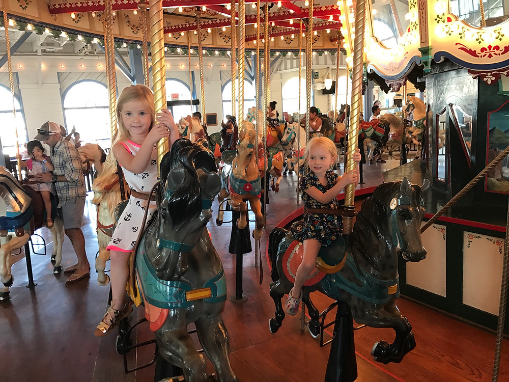 Emily and friend on a carousel at friend's birthday party