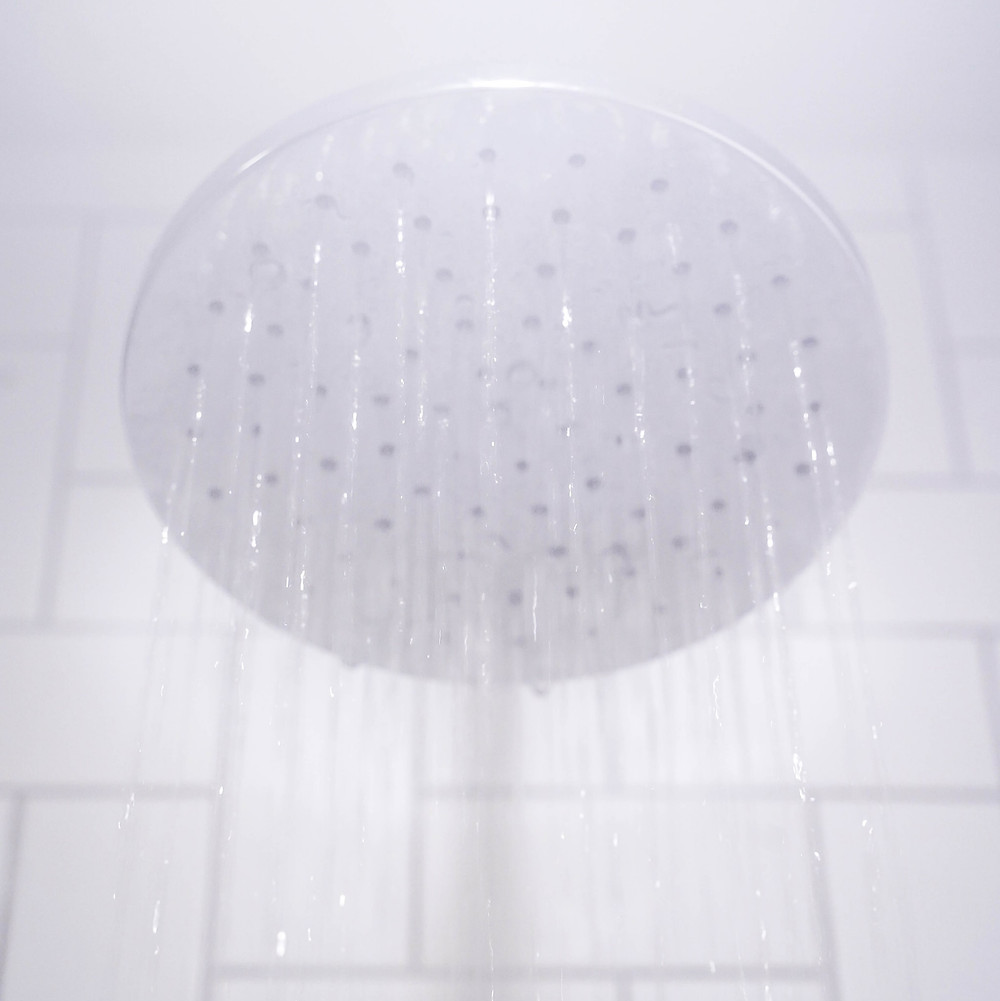 A shower head with water streaming from it.
