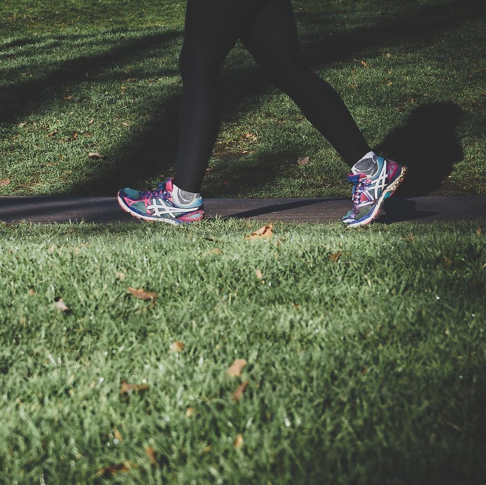 A person walking in sneakers on a sidewalk.
