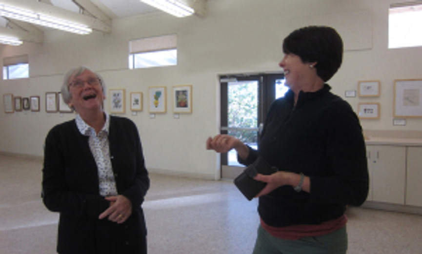 """Consider volunteering to help with the """"Artist's Favorite"""" SDBG exhibition—we have a good time. Photo of BAGSC members Joan Keesey (left) and Janice Sharp (right) enjoying a laugh during the hanging of the 2013 BAGSC exhibition at the SDBG."""