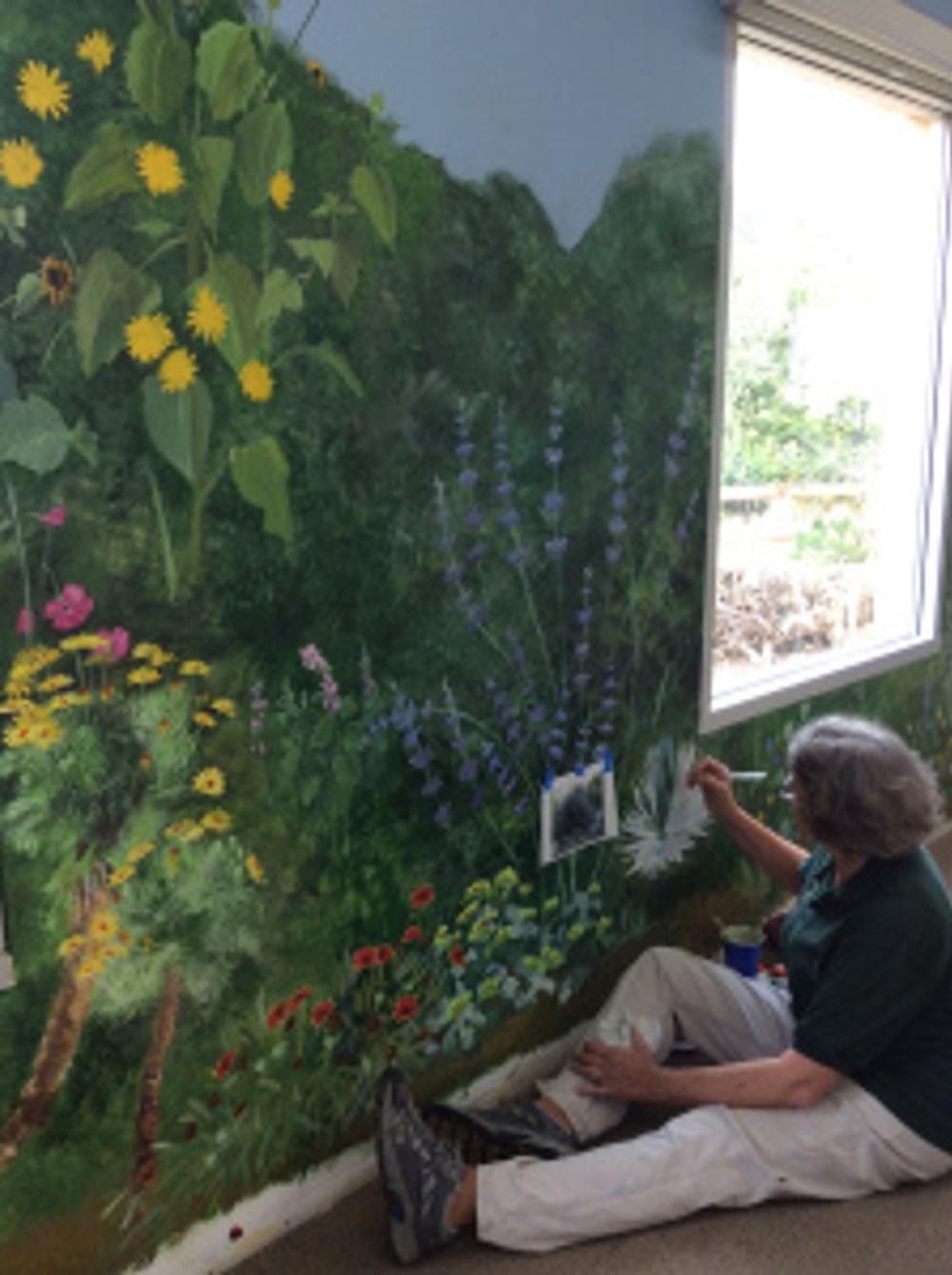 Estelle DeRidder adding details to the mural. Photo by Leslie Walker, © 2017.