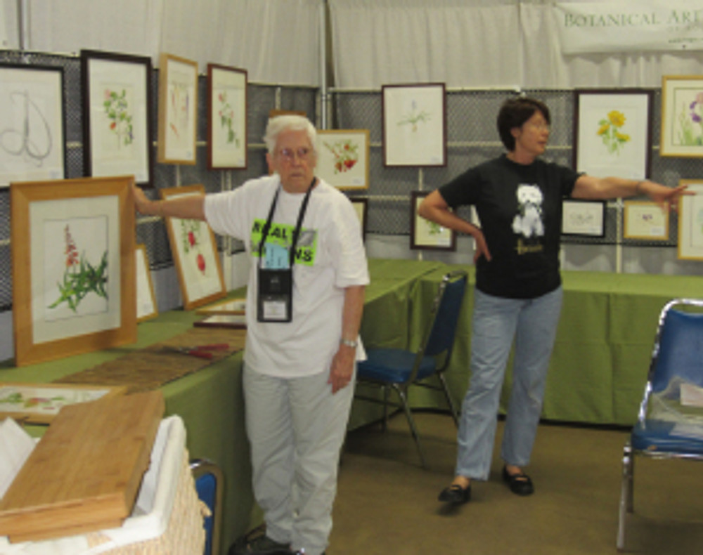 Leslie Walker and Janice Sharp give directions during the show hanging.