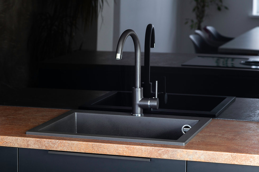 Black kitchen sink with a mixer in a kit