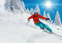 Skier skiing downhill in high mountains.