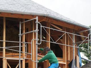 Remplissage de la structure bois avec les bottes de paille (37cm x 47cm x 90cm) provenant de leur propre exploitation agricole