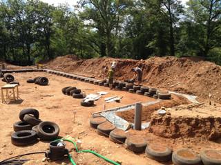 La terre du site est compactée dans des pneux pour créer des murs de soutènement.