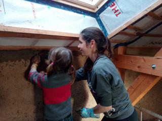 Toute la famille participe au chantier. Réalisation des enduits intérieurs en terre crue dans les chambres du premier étage.