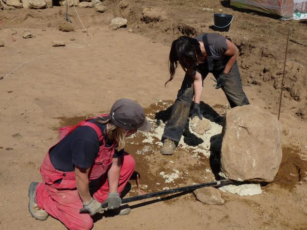 Anne Lequertier et Sarah Martin préparent le terrain. Les fondations sont réalisées avec les pierres du site.