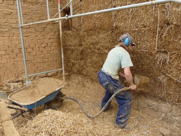 Le sol en cours de construction sera réalisé en terre crue. Anne Lequertier nivelle la première couche posée directement sur le gravier.
