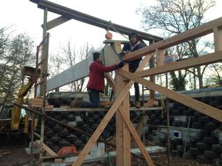 Après l'étape des pneus, les futurs habitants montent la charpente en bois accompagnés de l'expert Matthieu Guyomard.