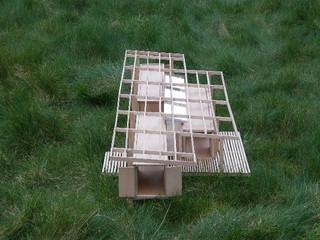 Maquette de recherche à l'échelle 1/50eme de l'architecte Catherine Rannou. Les trois conteneurs sont organisés sour une structure en bois qui porte la couverture et protége de la pluie.