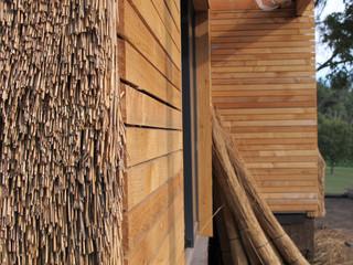 Finition extérieur mixte entre bardage bois et roseaux en façade.