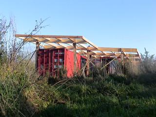 La toiture repose sur une structure en bois extérieure aux conteneurs. Cette charpente assure les fondations et la couverture des conteneurs.