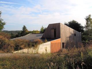 Maison en ossature bois et remplissage paille qui s'inscrit avec élégance dans le paysage du site.