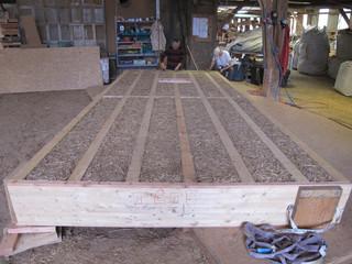 Préfabrication de caisson en bois remplissage roseaux en vrac dans l'atelier Echopaille.