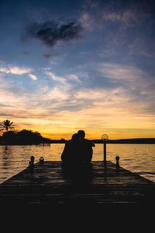Casal abraçado em pier na beira do lago ao pôr do sol