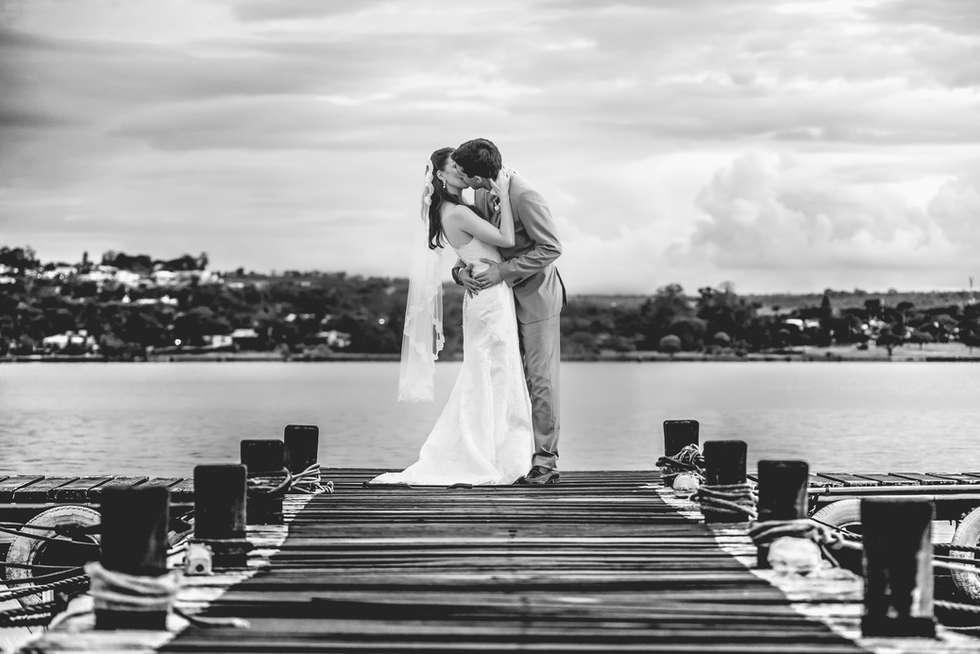 Noivos se beijando em um pier na beira do lago