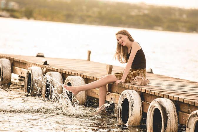 Ensaio fotográfico de 15 anos em pier na beira do lago, debutante