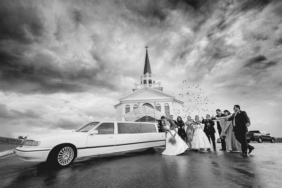 Casal com limousine em frente a igreja com padrinhos jogando pétalas