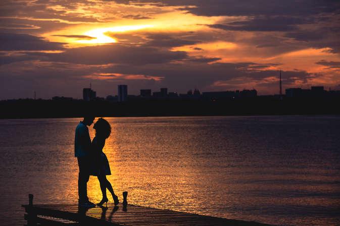 Casal em pier no lago ao pôr do sol