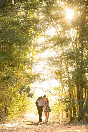Casal andando em caminho entre as árvores ao pôr do sol