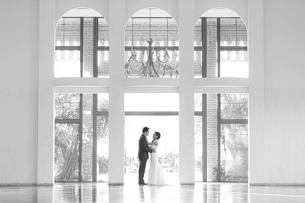 Noivos abraçados em salão com arco