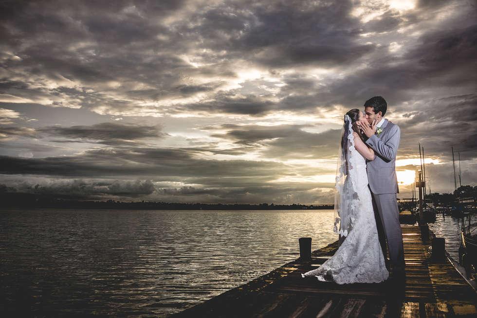 Noivos se beijando em um pier na beira do lago ao pôr do sol