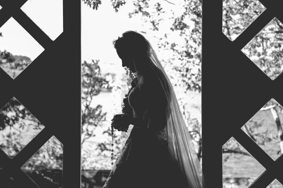 Silhueta de noiva rezando em capela