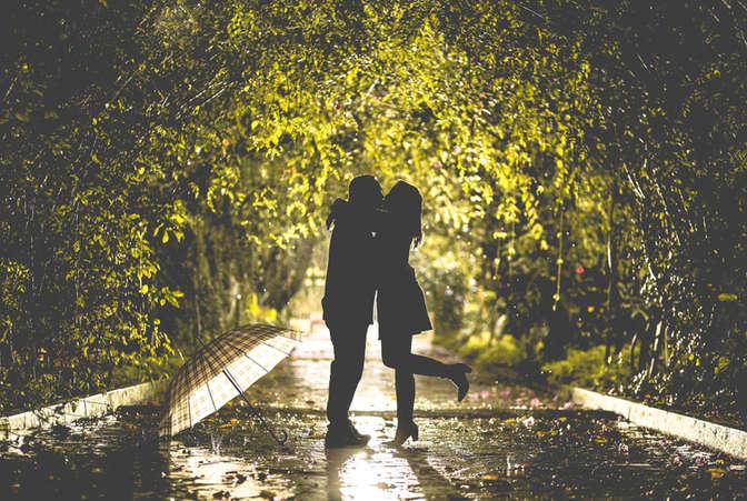 Casal se beijando em caimho em meio as árvores