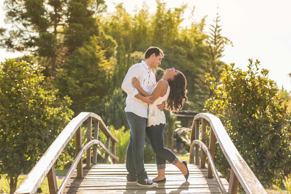 Casal rindo em ponte de madeira no Jardim Botânico