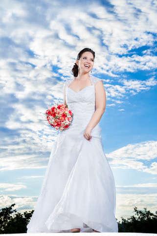 Noiva sorrindo com céu azul ao fundo
