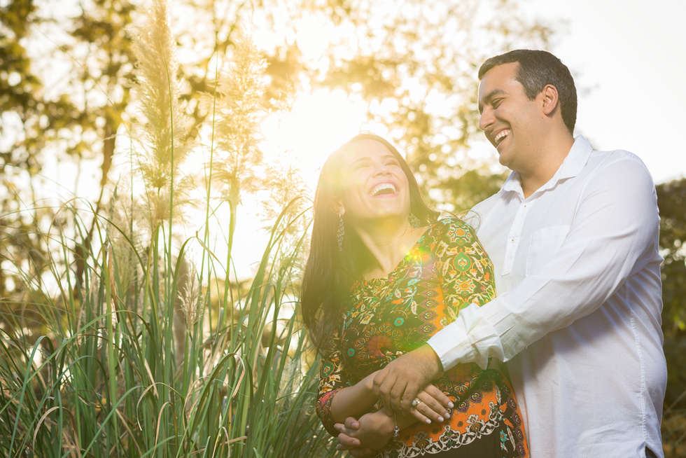 Casal abraçado rindo ao pôr do sol