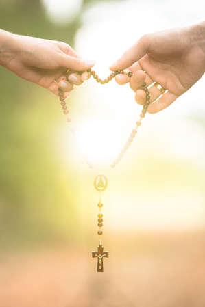 Casal segurando crucifixo, terço, rosário.