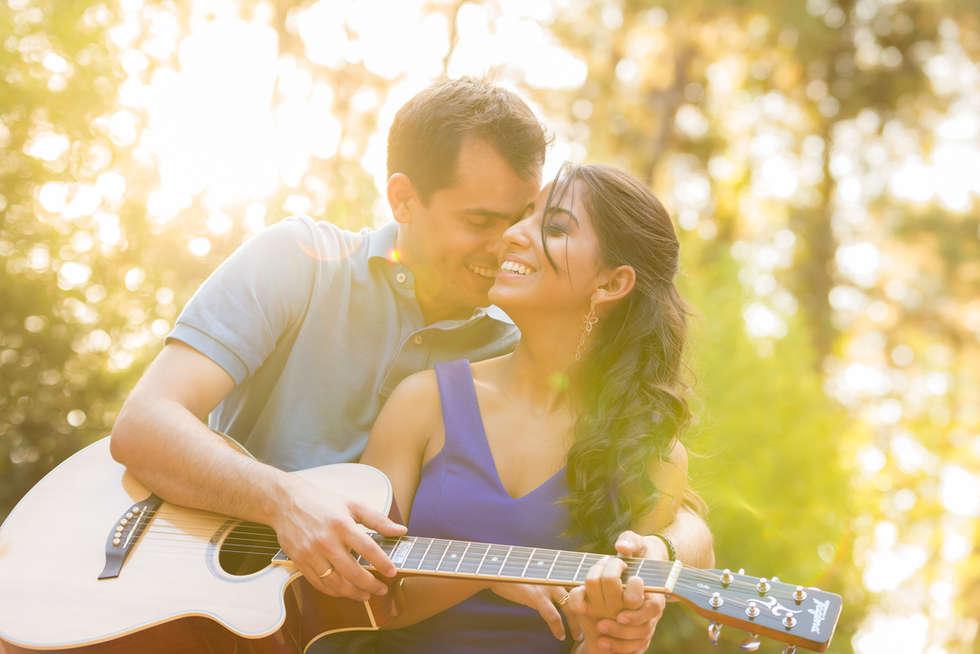 Casal com violão ao pôr do sol
