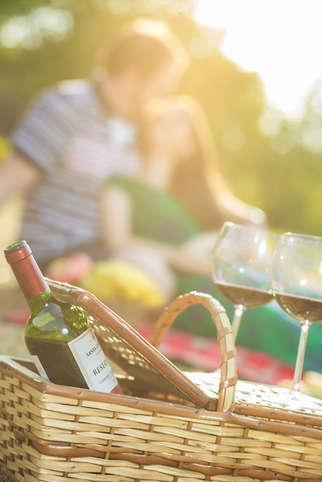 Casal fazendo picnic com vinho ao pôr do sol