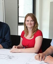 Ein junge Frau sitzt am Schreibtisch, lächelt, trägt ein rotes T-Shirt