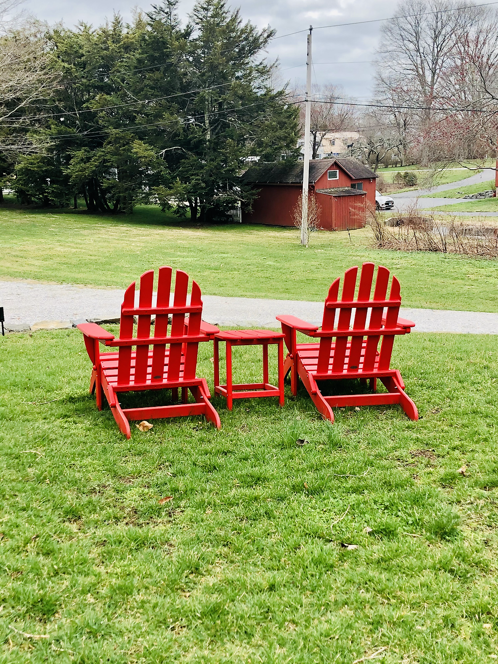 Two red wooden adirdondack chairs sit on a grassy yard facing a bit red bar and gravel driveway.