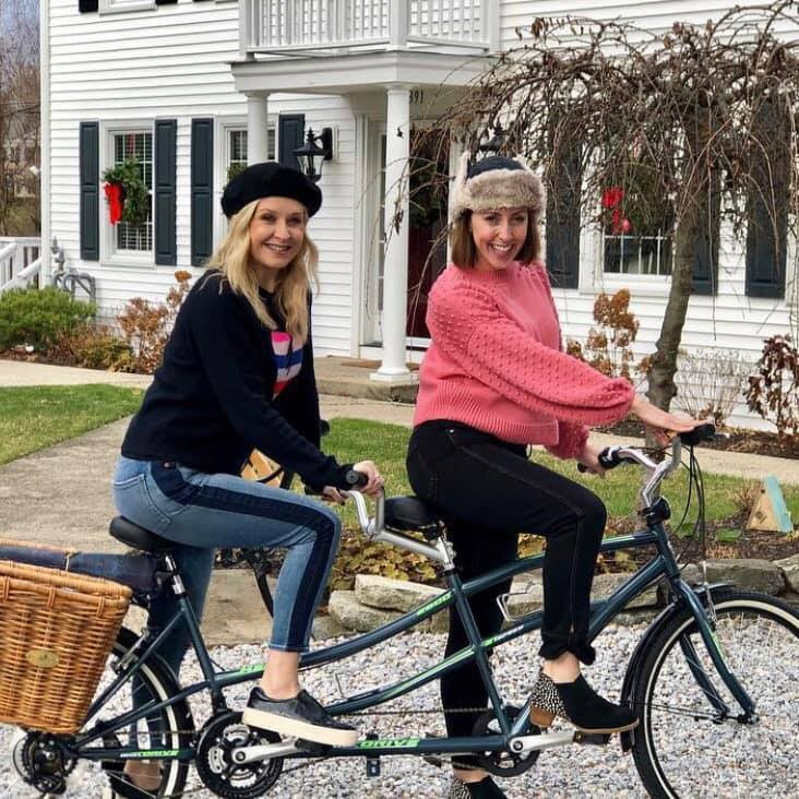Two woman sit on a tandem bicycle ready to enjoy a fall day.