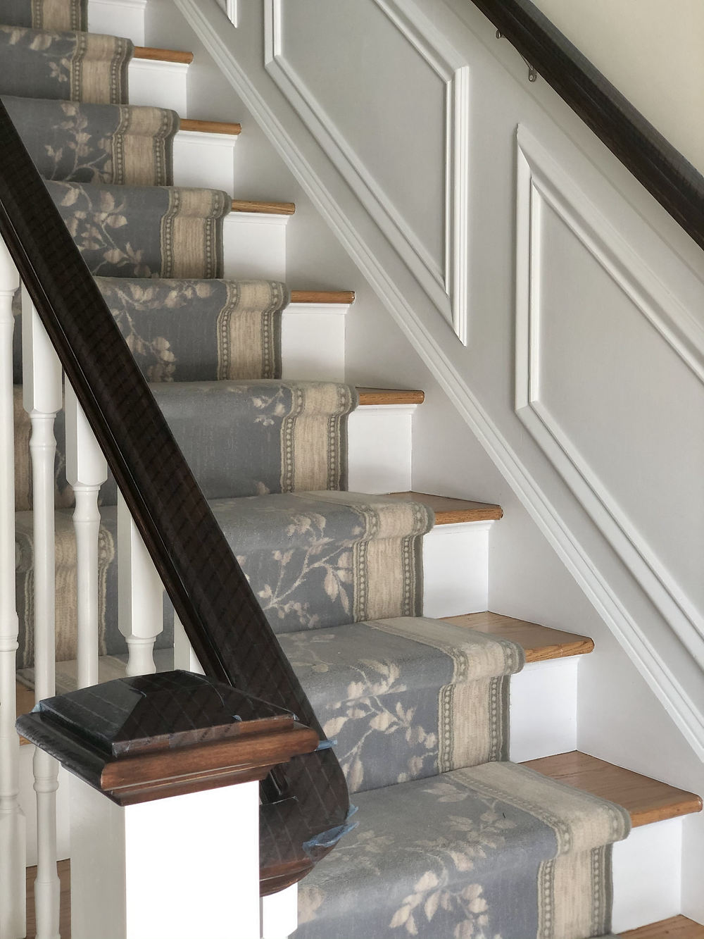 A dark wooden railing covered in antimicrobial tape flanks a beautiful wooden staircase with a floral carpet runner.