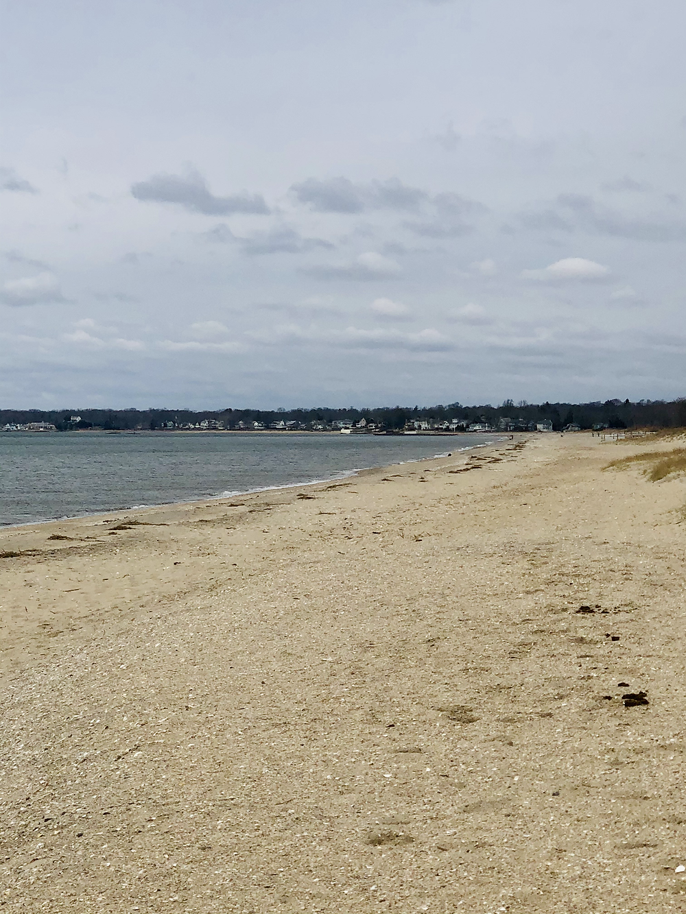 The blue waters and sandy shores of a beach on a cloudy day.