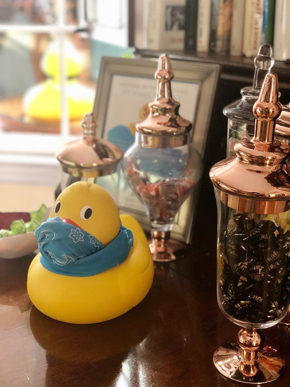 A yellow rubber Duckie wearing a face masks sits on a hutch surrounded by glass candy dishes filled with confections.