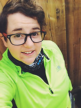 Begin image. A mature white person is stood in front of a wooden wall. She has short brown hair and black glasses. She is smiling at the camera and is wearing a neon yellow jackets that is unzipped slightly to show a black top underneath. End image.