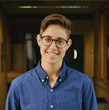 Begin image. A a young white person is smiling warmly at the camera. They are wearing a blue button down shirt, have short brown hair and is wearing black glasses. End image.