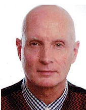 Begin image. A mature white man is looking into the camera with a small smile. He is bald and is infront of a white backdrop. End image.