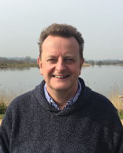 Begin image. A mature white man is smiling at the camera. He has short spikey greying hair and appears in front of a body of water. He is wearing a button down shirt underneath a grey jumper. End image.