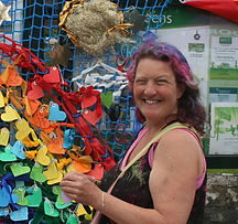 Begin image. A mature white woman stands to the right of a blue net with many coloured hearts hanging off it. She is facing left, with her head turned to the camera. Her arm is bent at a right angle and she is holding something in her hand. She has shoulder-length brown hair, and the top of her hair has been dyed purple and pink. She is wearing a black tank top with a pattern of tropical leaves, and a beige bag strap can be seen running across her body. She is smiling brightly and proudly, enough to crinkle her eyes. End image.