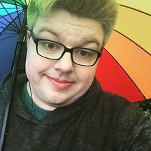 Begin image. A young man looking directly into the camera with his head tilted to the right. He has turquoise hair and is wearing a black hooded top and dark green t-shirt. He is wearing black, thick framed plastic glasses and is holding a multi-coloured umbrella which acts as the background of the picture. End image.