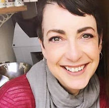 Begin image. A white middle aged woman with short brown hair is smiling into the camera.  She wears a red cardigan and black and white striped top with a grey scarf around her neck. End image.