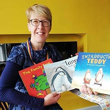 Begin image. A white woman in her 50s with glasses and short strawberry blonde hair beams at the camera.  She is holding up some of the books she uses when she talks to young children about how all families are different, but share the same love - The Family Book by Todd Parr, And Tango Makes Three by Peter Parnell and Justin Richardson, and Introducing Teddy by Jessica Walton. End image.